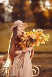 Young  woman  walking in autumn park with a bouquet of fall leav Royalty Free Stock Images