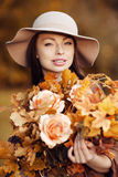 Young  woman  walking in autumn park with a bouquet of fall leav Stock Photography
