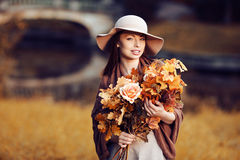 Young  woman  walking in autumn park with a bouquet of fall leav. Young fashion woman  walking in autumn park with a bouquet of fall leaves of maple and oak Royalty Free Stock Image