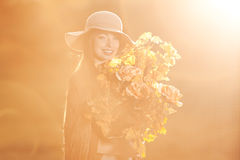 Young  woman  walking in autumn park with a bouquet of fall leav Royalty Free Stock Photos