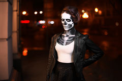 Young woman walking on avenue. Face art for Halloween party. Street portrait. Waist up. Night city background Royalty Free Stock Image