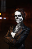 Young woman walking on avenue. Face art for Halloween party. Street portrait. Waist up. Night city background.  Royalty Free Stock Photos