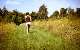 Young woman walking away in nature Royalty Free Stock Photography
