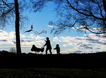 Young woman walking with baby stroller in park. Young woman walking with baby stroller and kite in park Royalty Free Stock Photography