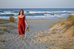 Young woman walking back from the sea Royalty Free Stock Photos