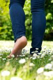 Young woman walking barefoot on green grass in the park Stock Photo