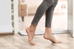 Young woman walking barefoot at home, closeup. Heating concept royalty free stock photography