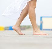 Young woman walking barefoot outdoors. Close up side view of a young woman walking barefoot outdoors Stock Photos