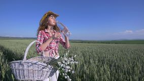 Young woman walking with basket with flowers and a bottle of water a wheat field with blue sky on the background. girl stock video