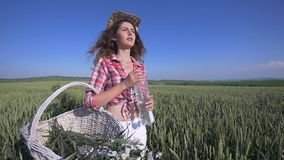Young woman walking with basket with flowers and a bottle of water a wheat field with blue sky on the background. girl stock video footage
