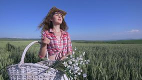 Young woman walking with basket with flowers and a bottle of water a wheat field with blue sky on the background. slow Royalty Free Stock Photography