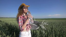 Young woman walking with basket with flowers and a bottle of water a wheat field with blue sky on the background. slow stock video