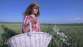 Young woman walking with basket with flowers and a bottle of water a wheat field with blue sky on the background. slow stock video footage
