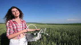 Young woman walking with basket with flowers a wheat field with blue sky on the background. slow motion stock footage