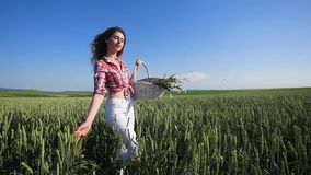 Young woman walking with basket with flowers a wheat field with blue sky on the background. slow motion stock video footage