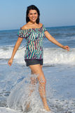 Young woman walking on beach stock photo