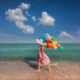 Young woman walking on the beach with colored balloons / Relax Stock Image