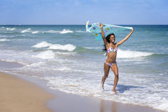 Young woman walking on the beach with a colored sarong Royalty Free Stock Image