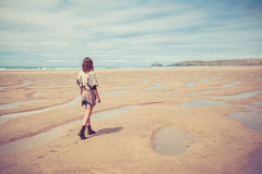 Young woman walking on the beach Stock Images
