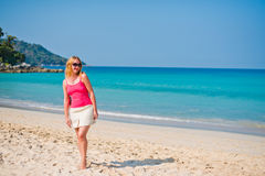 Young woman walking on beach Stock Images