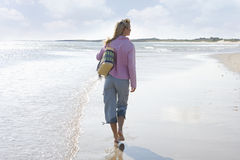 Young woman walking on beach, rear view Royalty Free Stock Photos