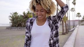 Young woman walking on a beach with a skateboard stock video