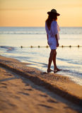 Young woman walking on the beach at sunrise Royalty Free Stock Images