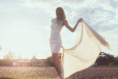Young woman walking on beach under sunset light,. Outdoors portrait. Soft light and Sunshine Stock Photography