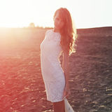 Young woman walking on beach under sunset light,. Outdoors portrait. Soft light and Sunshine Royalty Free Stock Images