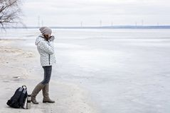 Young woman walking on beach watching the frozen water and drinks hot tea. Walk the river shore Royalty Free Stock Photo
