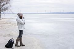 Young woman walking on beach watching the frozen water and drinks hot tea. Walk the river shore Stock Images