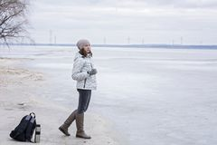 Young woman walking on beach watching the frozen water and drinks hot tea. Walk the river shore Royalty Free Stock Image