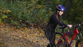Young woman walking with a bicycle in the autumn park.  stock footage
