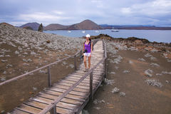 Young woman walking on a boardwalk on Bartolome island, Galapago Stock Photo