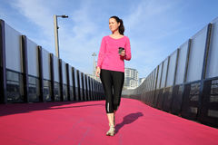 Young woman walking on a bright pink road. Young woman & x28;age 30& x29; walking with coffee on a bright pink cycleway road in Auckland, New Zealand.  Real Royalty Free Stock Images