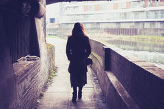 Young woman walking by canal under a bridge Stock Images