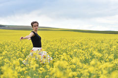 Young woman walking through a canola field. Freedom concept Royalty Free Stock Image