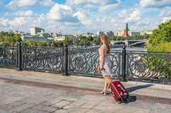 Young woman walking and carrying a suitcase in Moscow Royalty Free Stock Photography