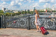 Young woman walking and carrying a suitcase in Moscow Stock Photo