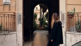 Young woman walking in the city centre. Brunette girl looking around, exploring city. Female comes in arch. Slow motion. Young woman walking in the city centre stock footage