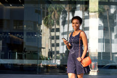 Young woman walking in city with earphones and mobile phone Royalty Free Stock Photo