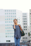 Young woman walking in the city making phone call. Portrait of young woman walking outdoors and making a phone call in the city Royalty Free Stock Images