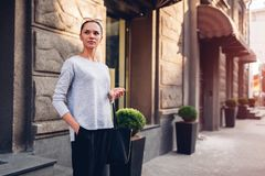 Young woman walking on city street. Girl wearing stylish clothes and accessories royalty free stock photo
