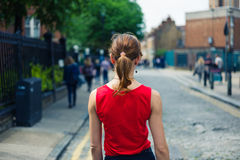 Young woman walking on cobbled street in summer Royalty Free Stock Photo