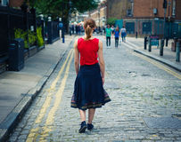Young woman walking on cobbled street in summer Royalty Free Stock Images