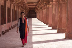 Young woman walking in colonnade walkway Stock Photos