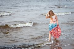 A young woman walking in the colorful long gown along the seafro royalty free stock photos