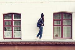 Young woman walking on cornice Royalty Free Stock Image