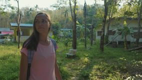 Young woman walking on countryside path through asian village, slow motion. Steadicam portrait shot of young backpacker woman walking alone on a countryside stock video footage
