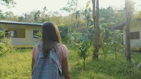 Young woman walking on countryside path through asian village, slow motion. Steadicam shot of young backpacker woman walking alone on a countryside path through stock video footage